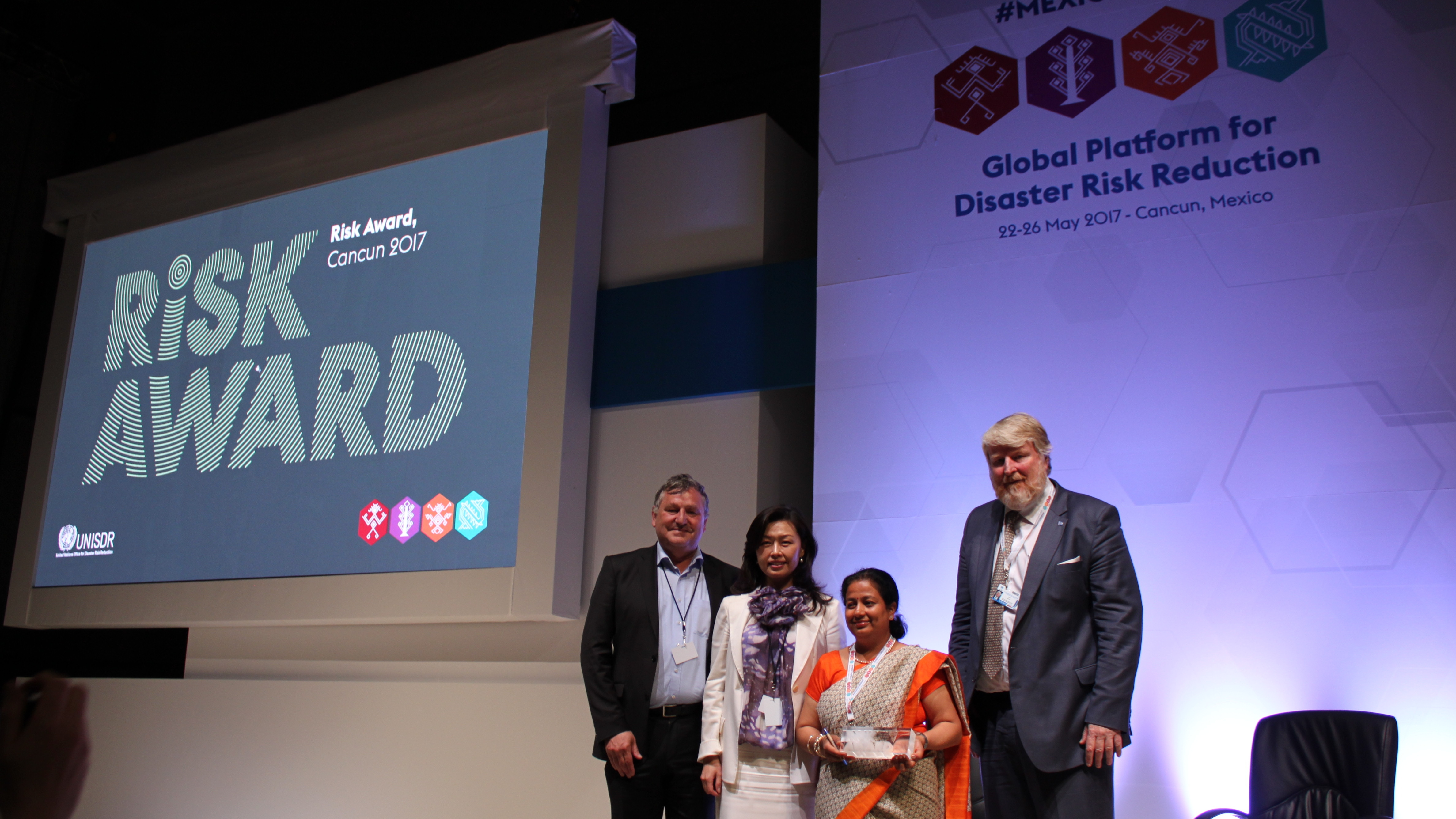 Thomas Loster (Munich Re Foundation) and Sandra Wu (RISK Award jury member) handed over the trophy to Apsara Pandey. The session was hosted by UNISDR, represented by David Stevens (right).